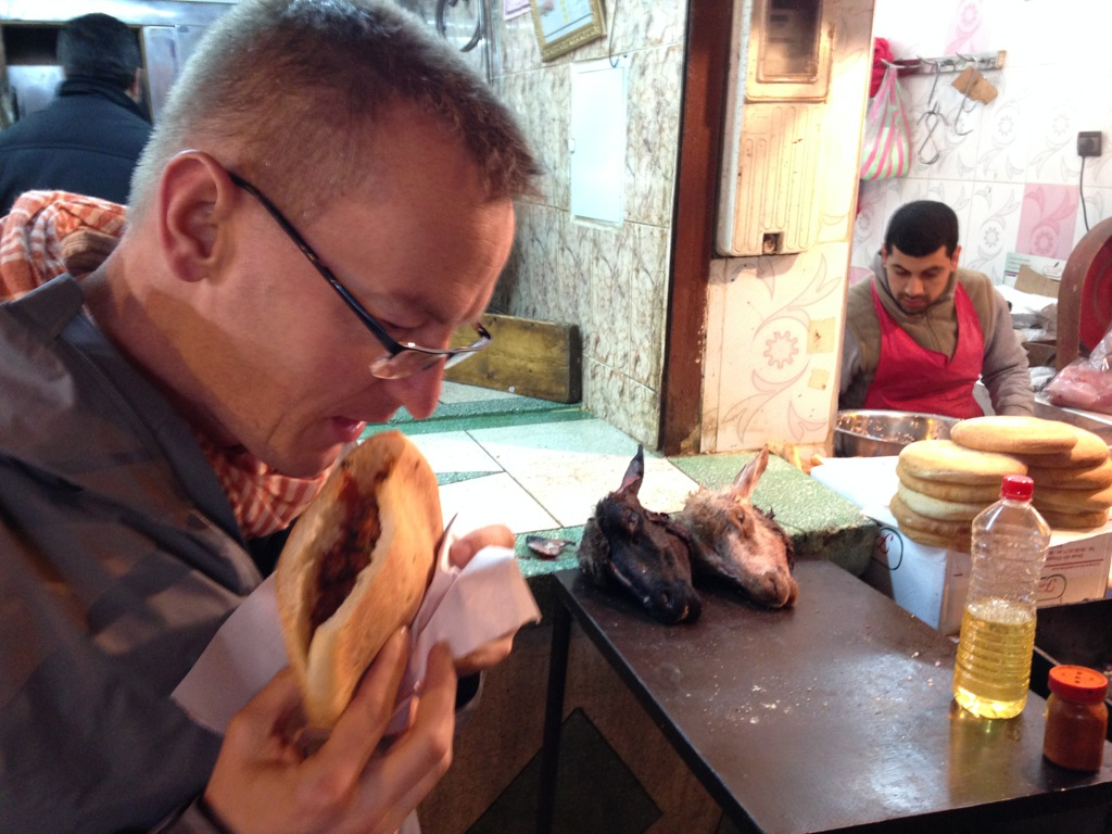 Chris enjoys a sausage sandwich, undaunted by the onlooking goat's heads