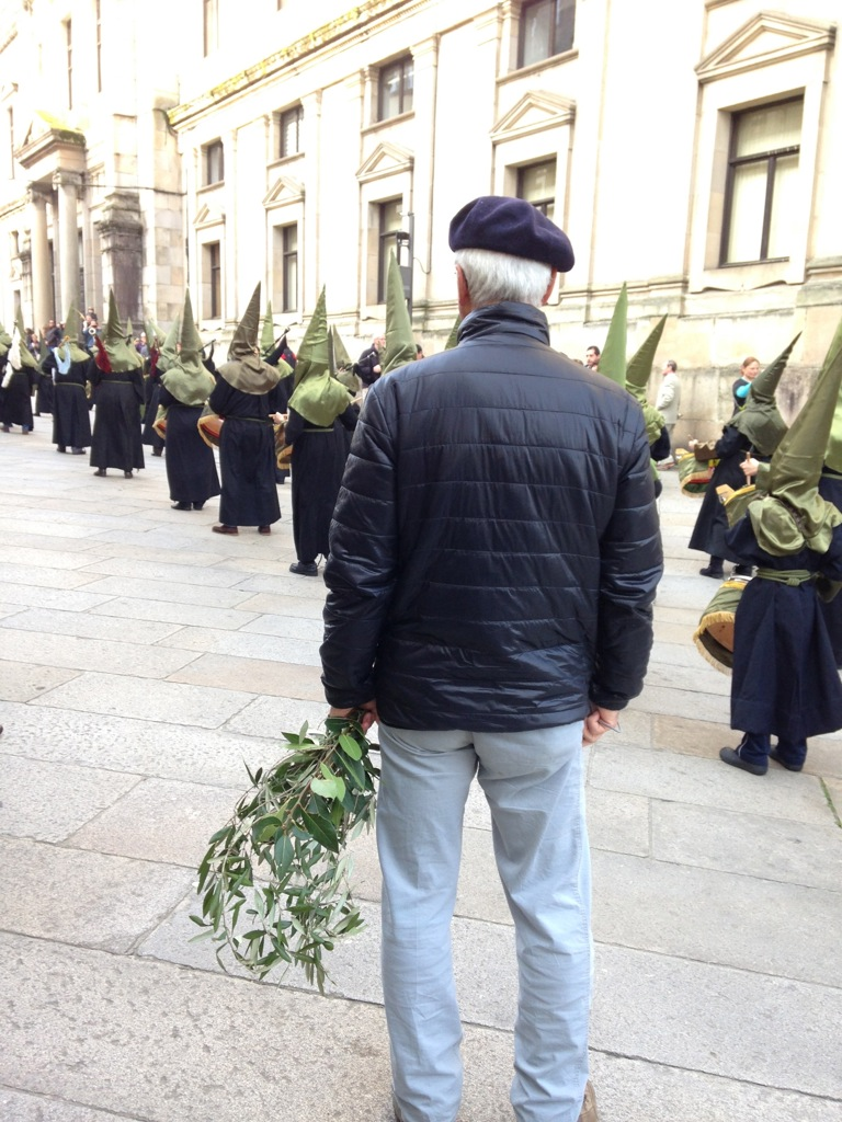 An onlooker with olive branches observes the procession