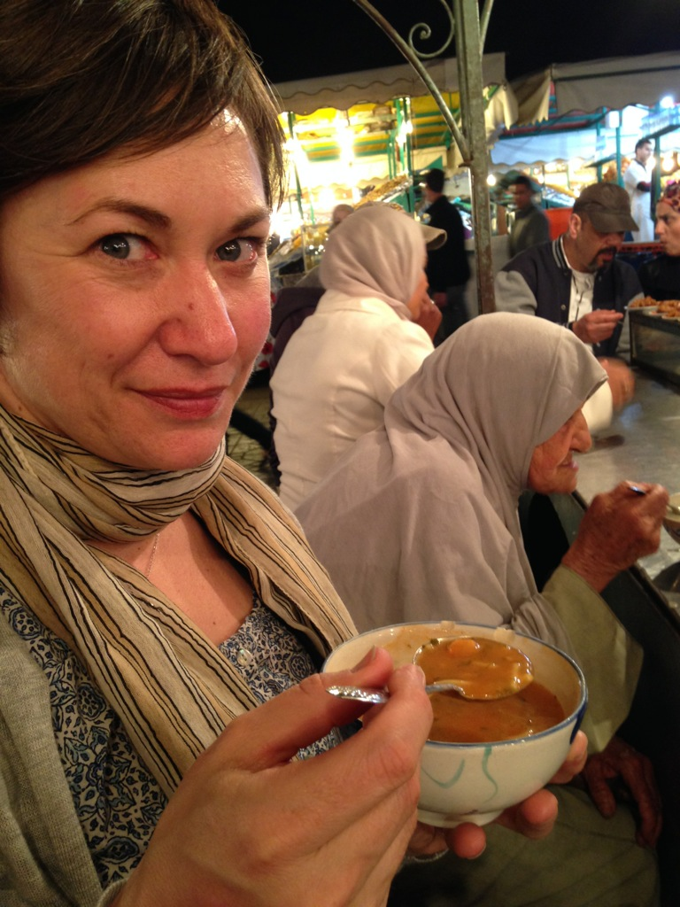 Alison in Marrakech, Morocco eating soup alongside a very old woman.