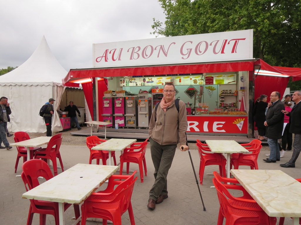 Chris, with crutch, poses in front of an aptly and unfortunately named Bordeaux street eatery