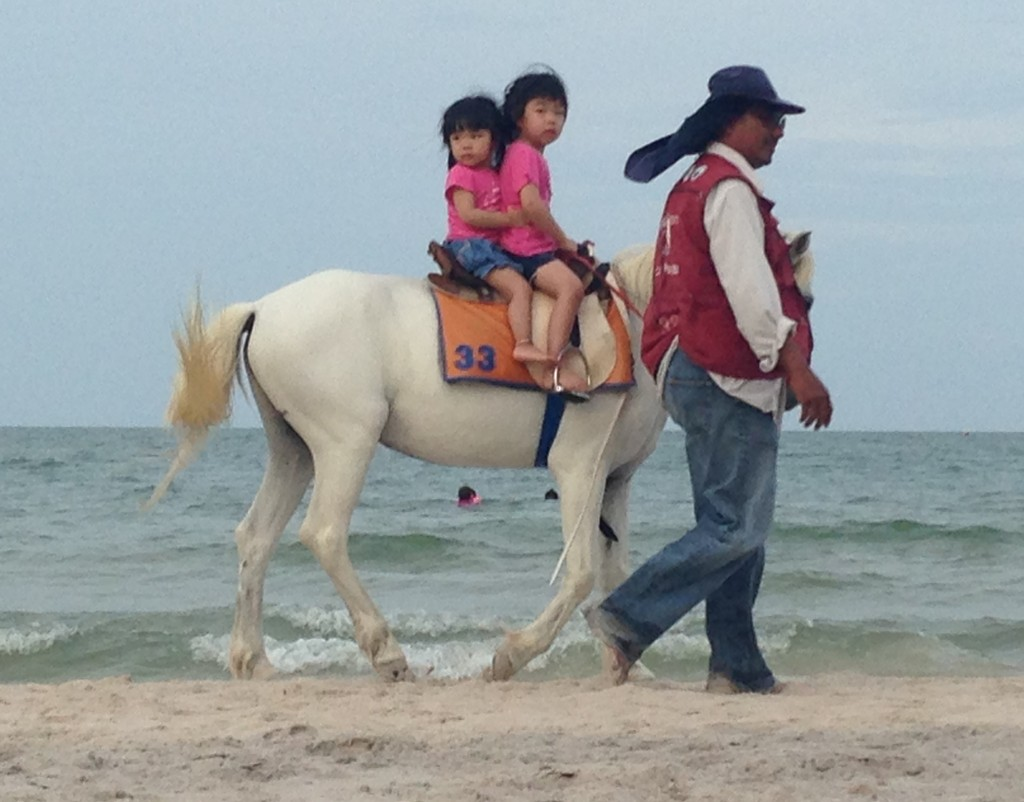 A Groom Leads Two Children on Horesback at Hua Hin Beach