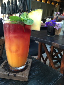 A red and orange layered cocktail served with a slice of pineapple beside the Chao Phraya river in Bangkok