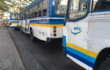 Buses painted blue, white, and yellow await commuters at the Memorial Bridge ferry terminal in Bangkok.